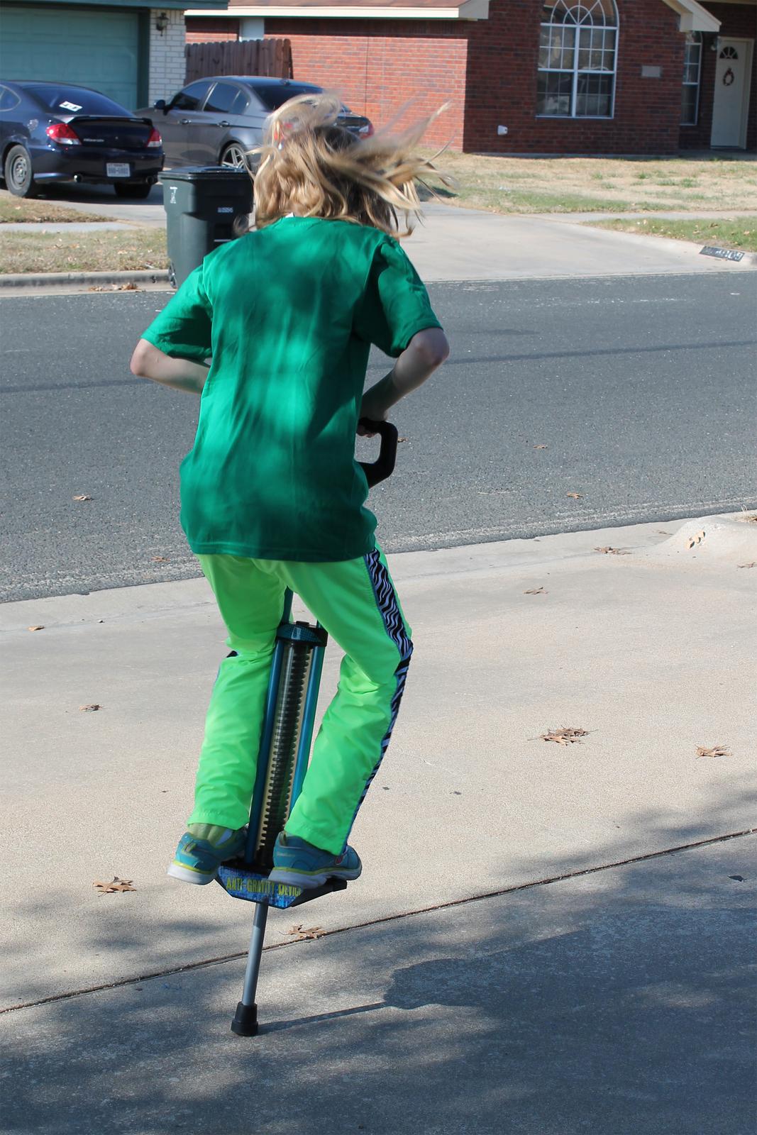 Fotografia dziecka skaczącego na zabawce pogo.