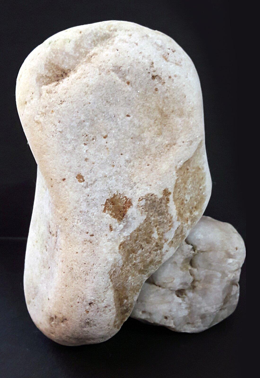 Ilustracja przedstawiająca surowy blok zmarmuru. Kamień jest koloru jasnego na czarnym tle.