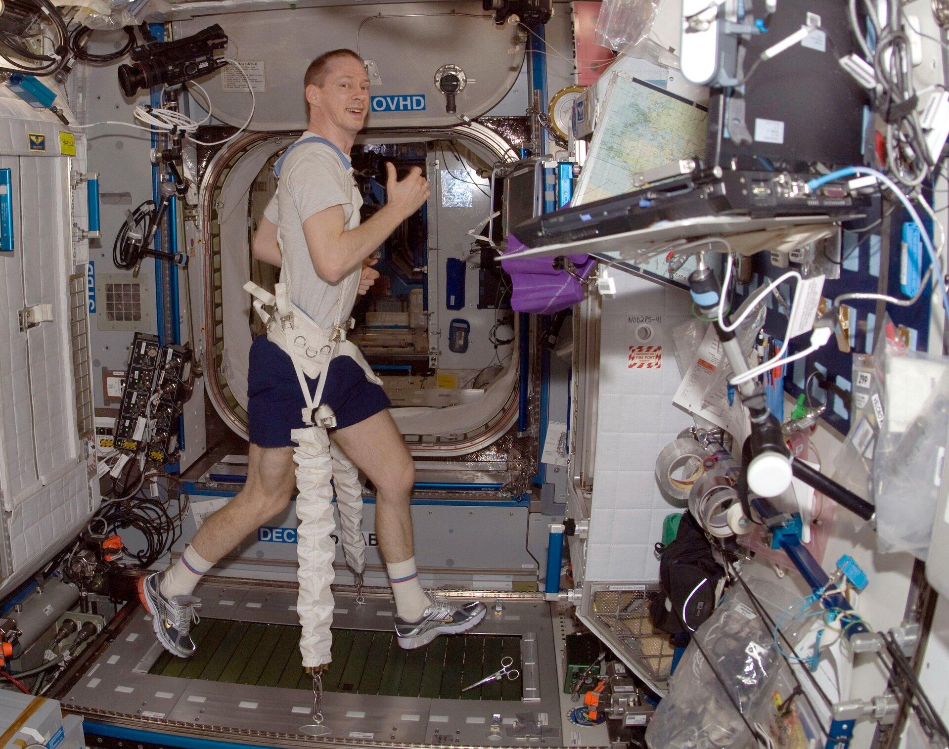 Zdjęcie przedstawia kosmonautę wykonującego ćwiczenia na bieżni magnetycznej wewnątrz stacji kosmicznej. Mężczyzna wwieku ok. 35 lat. Widoczny prawy bok ciała. Szatyn, włosy krótko przystrzyżone. Ubrany wszarą koszulkę zkrótkim rękawem typu T-shirt oraz granatowe spodenki. Na nogach obuwie sportowe typu adidas ibiałe skarpetki. Mężczyzna uśmiecha się. Mężczyzna na biodrach ma szeroki biały pas, do którego przypięto uprząż mocującą go nad bieżnią.