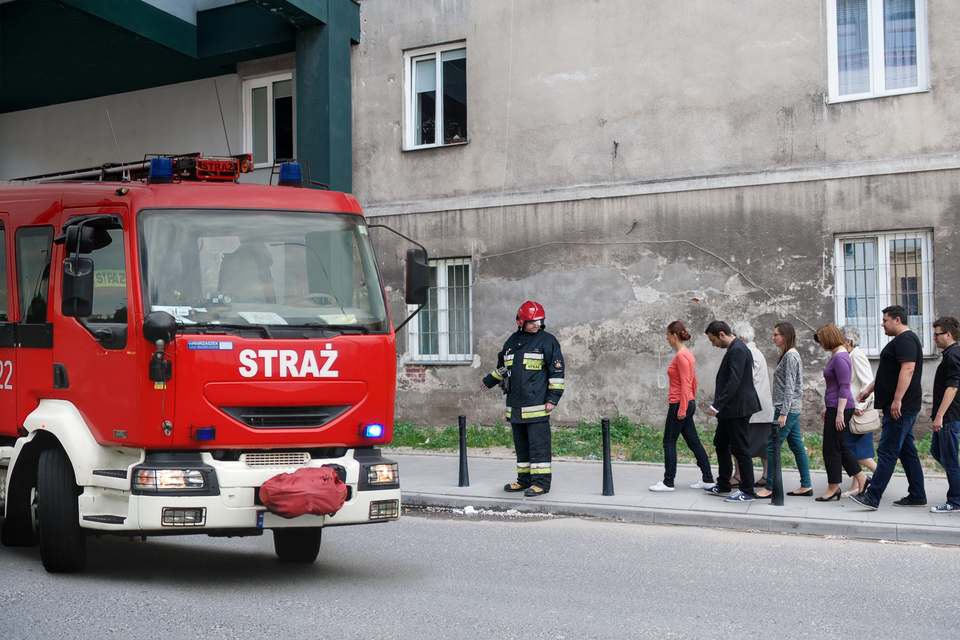 Zdjęcie przedstawia ewakuację grupy ludzi zbudynku. Ulica. Słoneczny dzień. Na pierwszym planie, po lewej stronie, czerwony wóz strażacki. Wóz strażacki skierowany wprawo. Na prawo od wozu, chodnik. Wzdłuż chodnika prowadzeni są mieszkańcy. Zprzodu grupy strażnik. Strażnik ubrany wkombinezon ochronny oraz czerwony kask. Za ludźmi, wtle zdjęcia, wysoki szary budynek.