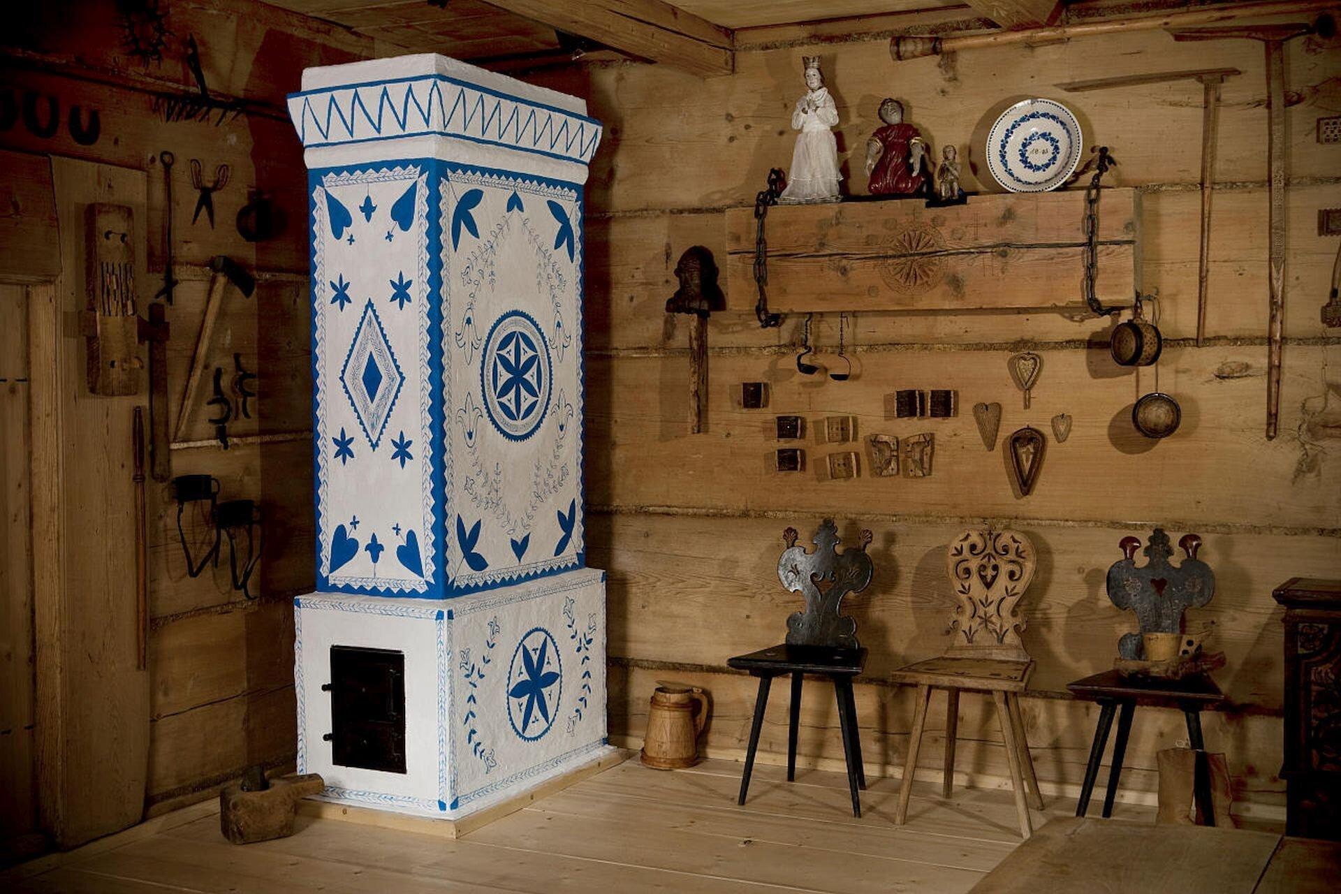 Ilustracja przedstawia wnętrze muzeum zakopiańskiego. Jest to drewniane pomieszczenie gdzie wrogu stoi biały, wniebieskie wzory piec kaflowy. Na ścianach wiszą różne przedmioty domowego użytku iozdoby. Na podłodze pod ścianą stoją trzy krzesła ze zdobionymi oparciami. Obok pieca stoi drewniane naczynie na wodę.