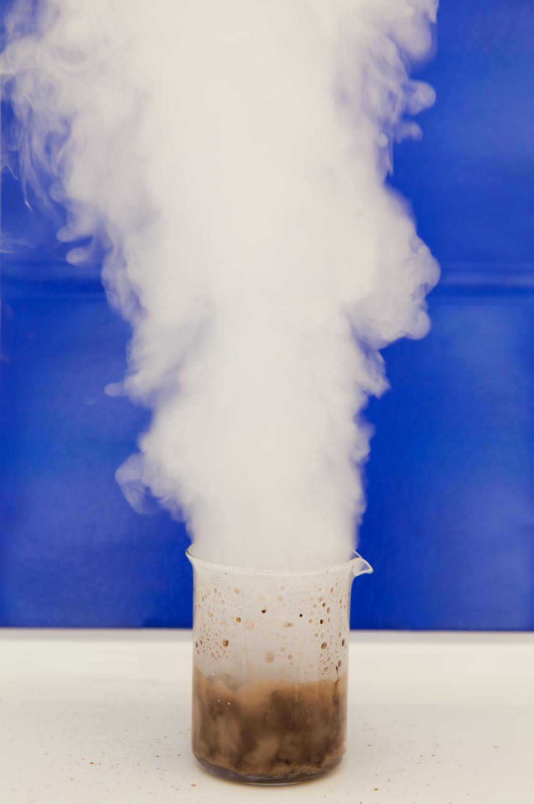 Zdjęcie przedstawia reakcję chemiczną perhydrolu zmanganianem siedem potasu. Stojąca na białym blacie zlewka pełna jest brązowobeżowej kipiącej substancji, zktórej unosi się słup gęstego, białego dymu. Na ściankach naczynia idookoła niego na blacie są też brązowe ślady kropel, dowód na to, że podczas reakcji dochodziło do silnych rozprysków.