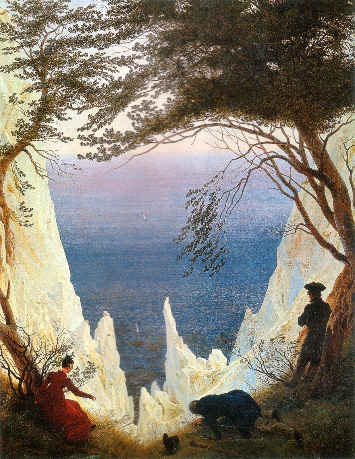 """Ilustracja okształcie pionowego prostokąta przedstawia obraz Caspara Davida Friedricha """"Skały kredowe wRugii"""". Ukazuje pejzaż skał zwidokiem na morze. Po bokach zamykają go drzewa, tworzące zkoron baldachim. Wdolnej części znajdują się trzy postacie – dwaj mężczyźni ijedna kobieta wczerwonej sukni. Przez prześwit pomiędzy białymi skałami widoczne jest niebiesko-fioletowe morze."""