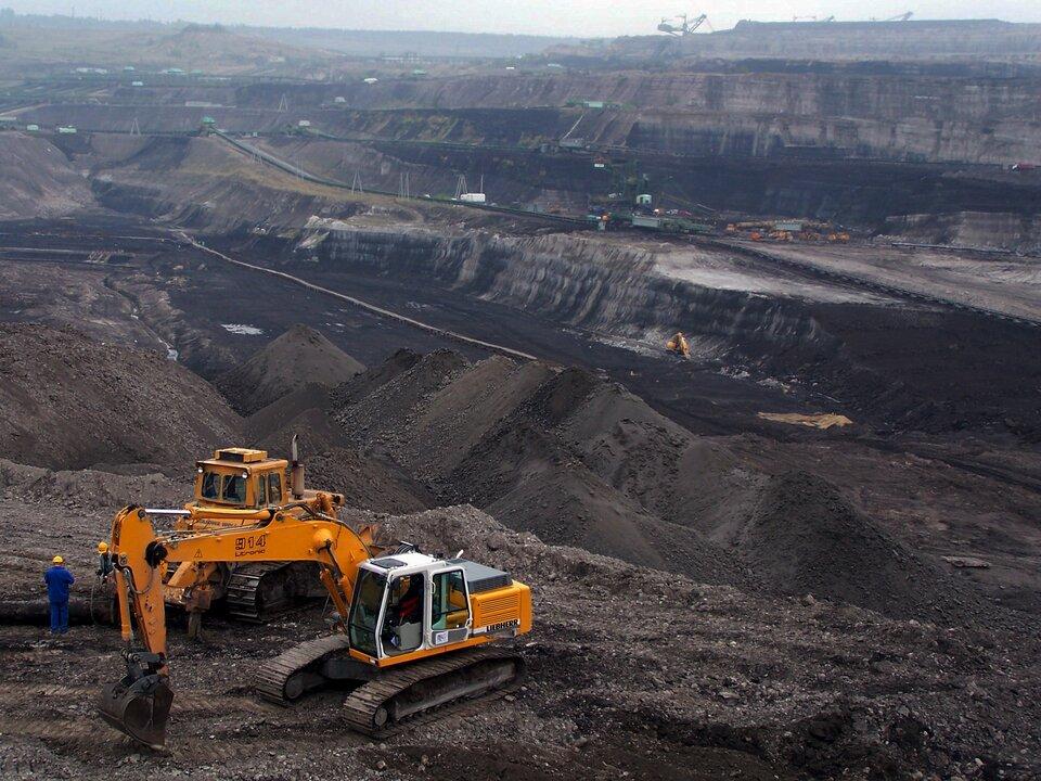 Fotografia prezentuje olbrzymie wyrobisko węgla kamiennego. Na pierwszym planie widoczne żółte koparki.