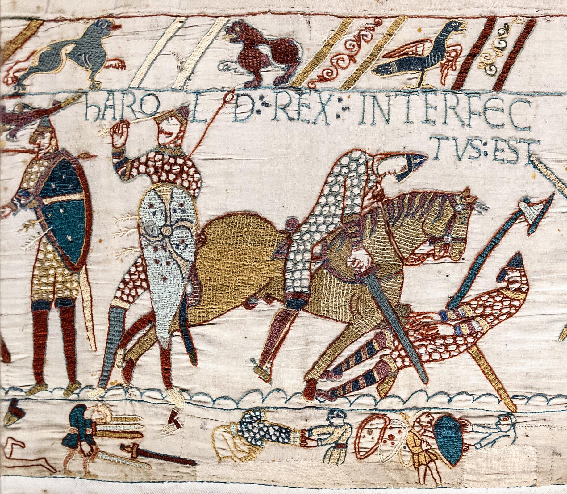 Ilustracja interaktywna przedstawia fragment tkaniny zBayeux. Ukazuje podbój Anglii przez Wilhelma Pierwszego Zdobywcę. Na ilustracji przedstawieni są czterej rycerze: dwaj po lewej trzymają wrękach tarcze zwbitymi wnie strzałami, po prawej rycerz na koniu zabija wroga wymierzając cios mieczem wprzeciwnika. Nad nimi zamieszczony jest pas zsymbolami zwierzęcymi oraz napis wjęzyku łacińskim. Na dole ukazane są miniatury ze sceny walki. Na ilustracji umieszczony jest interaktywny punkt zprzedstawieniem całej tkaniny, która zawiera pięćdziesiąt osiem scen przedstawiających historię podboju Anglii przez Wilhelma Zdobywcę. Ukazują one tysiąc postaci, realistycznie odwzorowane zwierzęta oraz przedmioty codziennego użytku. Normanowie przedstawieni zostali jako osoby okrótkich włosach iogolonych twarzach, natomiast ich anglosascy przeciwnicy mają długie włosy iwąsy.