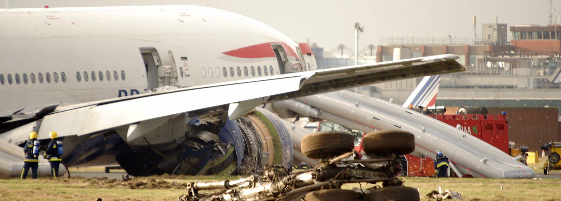 Kolorowe zdjęcie przedstawiające katastrofę samolotu pasażerskiego. Na pierwszym planie widoczne są oderwane koła podwozia, strzaskane silniki samolotu, stojący na ziemi biały kadłub samolotu. Do przedniego wyjścia zsamolotu podłączona jest dmuchana zjeżdżalnia awaryjna. Drugie wyjście awaryjne, środkowe, też jest otwarte. Po lewej stronie rozbitego samolotu stoi dwóch strażaków, po prawej – przy zjeżdżalni – pochyla się trzeci strażak. Wgłębi zdjęcia budynki lotniska.