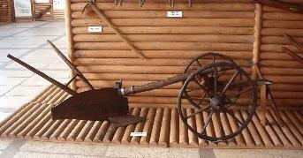 Obraz przedstawia dwukołowy wózek zkabłąkiem zpoprzeczką oregulowanej wysokości, na którym wspiera się grządziel pługa iradło.