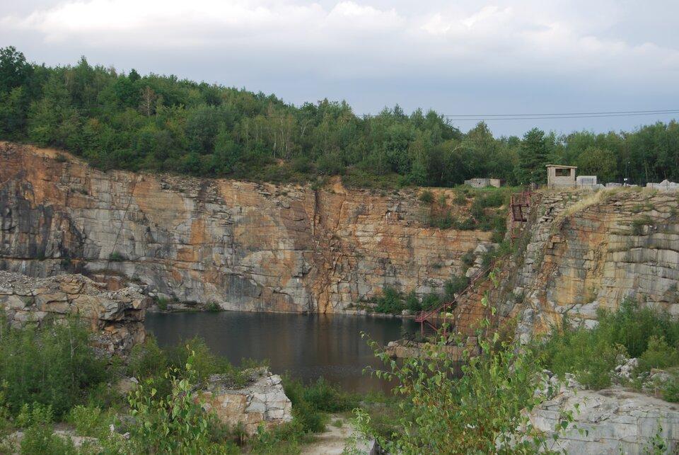 Na zdjęciu kamieniołom, strome skaliste zbocza. Zagłębienie wypełnione wodą.