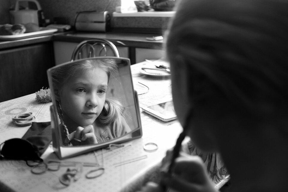 Czarnobiałe zdjęcie przedstawiające dziewczynkę przeglądającą się wmałym lusterku stojącym na stole kuchennym. Ostrość zdjęcia skupiona jest na odbiciu twarzy dziewczynki wcentralnej części kadru. Sama dziewczynka zwijająca włosy wwarkoczyki po prawej stronie kadru ukazana jest nieostro ityłem do obserwatora zdjęcia. Na stole wokół lustra gumki, spinki iinne akcesoria do upinania włosów. Wtle blat kuchenny ileżące na nim przedmioty wobszarze nieostrości, aprzez to nie do końca rozpoznawalne.