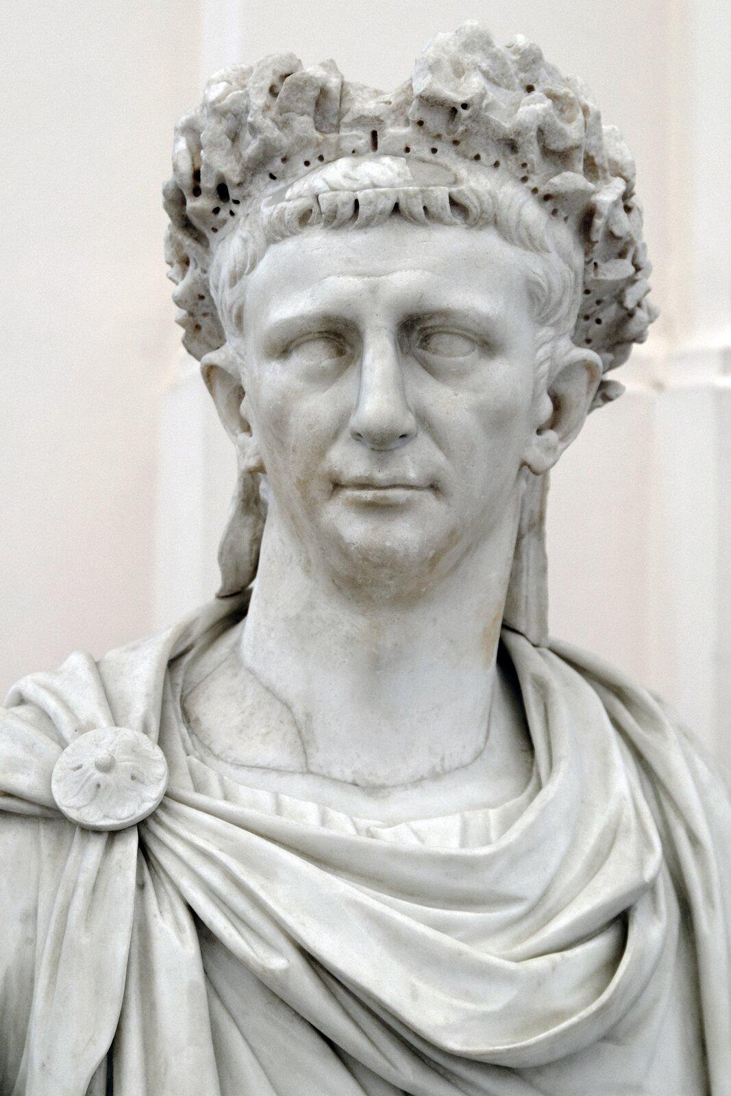 Ilustracja przedstawia marmurowe popiersie cesarza Klaudiusza. Ubrany jest wszatę spiętą na ramieniu klamrą. Ma małą głowę, lekko odstające uszy idość duży nos. Na głowie ma koronę