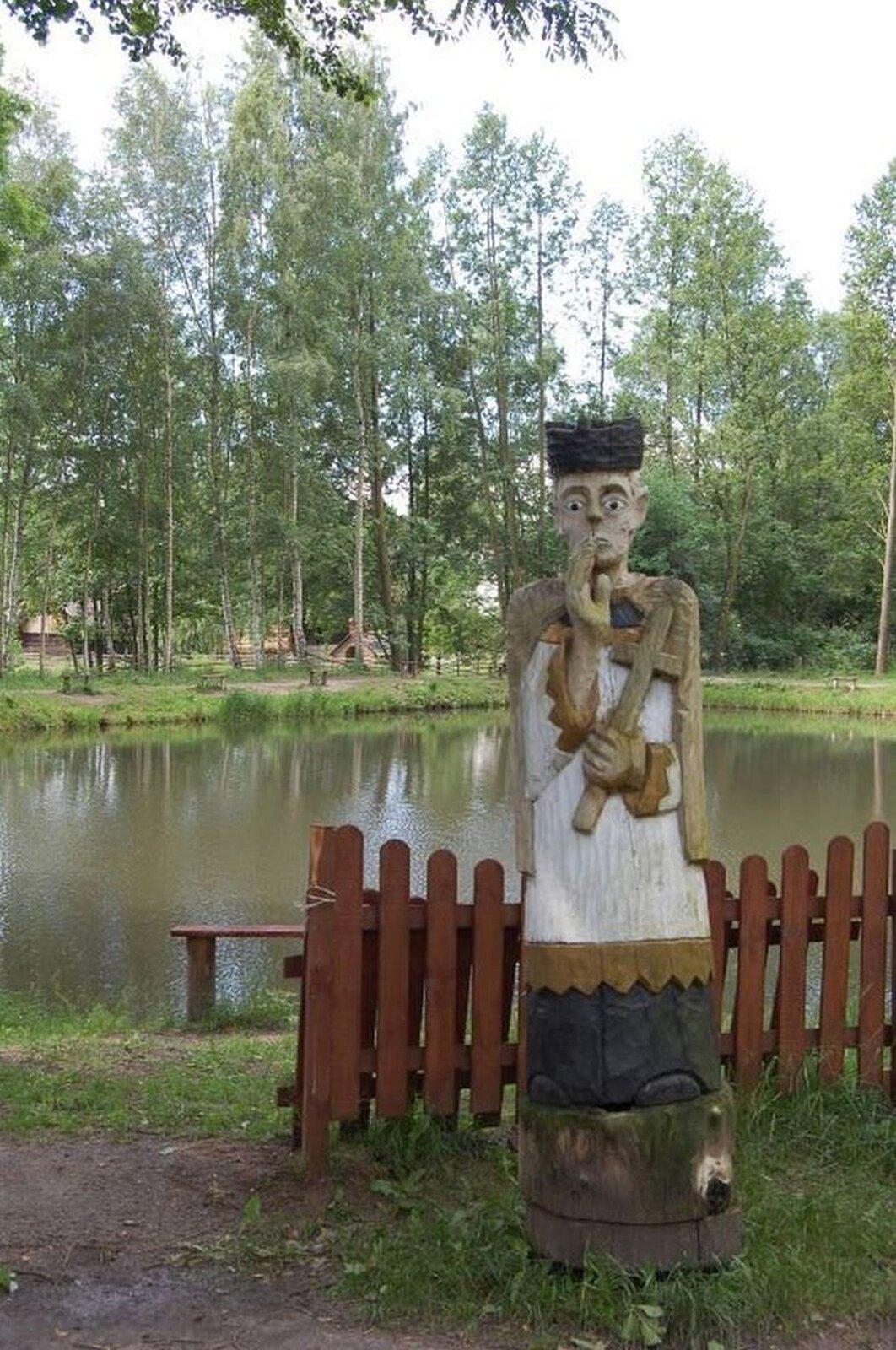 Ilustracja przedstawia figurę świętego Jana Nepomucena. Wjednej dłoni trzyma krzyż, adrugą ma uniesioną wgeście błogosławieństwa. Na głowie ma czarny biret. Jest ubrany wbiałą komżę, spod której widać jeszcze czarną sutannę. Rzeźba stoi na tle jeziora idrzew. Tuż za figurą stoi nieduży płotek.