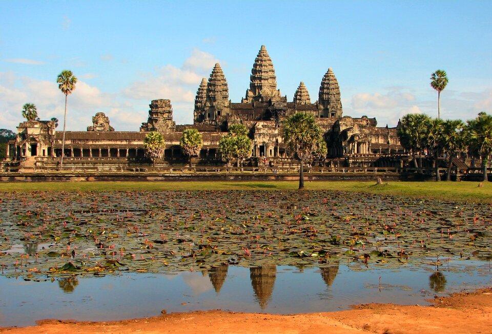 Na zdjęciu świątynia zwieloma wysokimi wieżami, wiele detali. Przed nią zbiornik wodny, lilie wodne.
