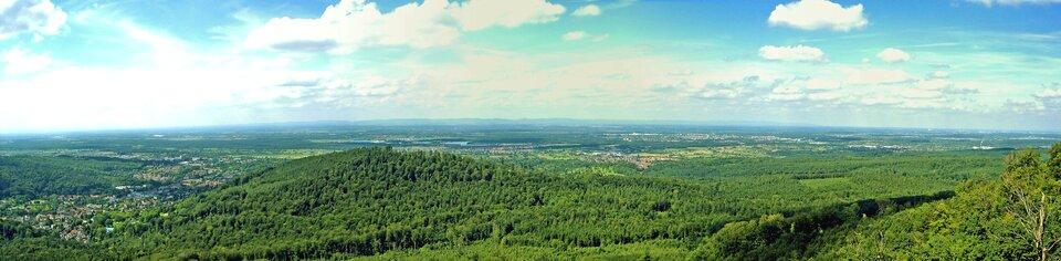 Na zdjęciu panoramicznym rozległy płaski, lekko pofałdowany teren porośnięty lasem.