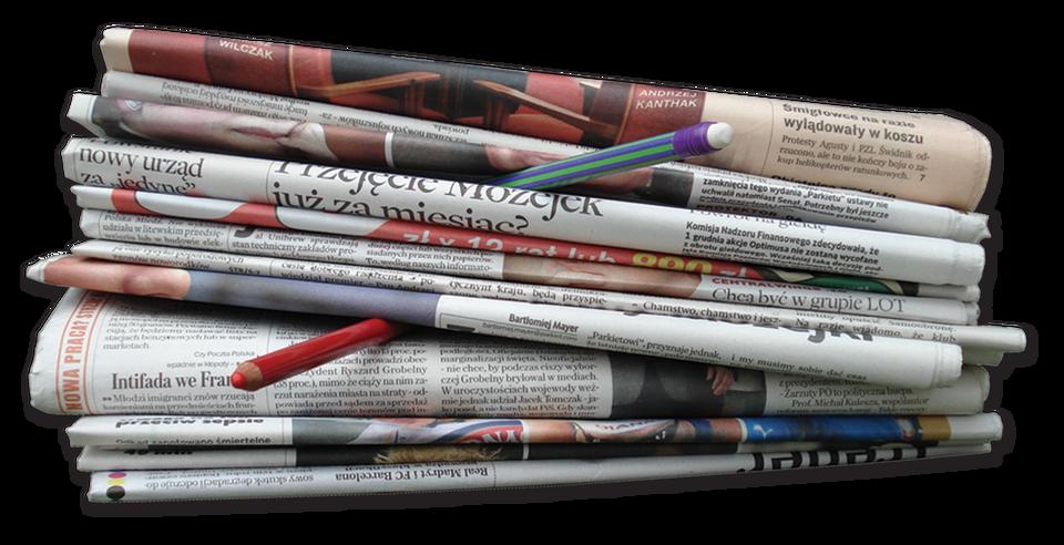 Na zdjęciu stosik codziennych gazet. Na czwartej od dołu gazecie leży czerwona kredka, ana dziewiątej, zielono-fioletowy ołówek zbiałą gumką.