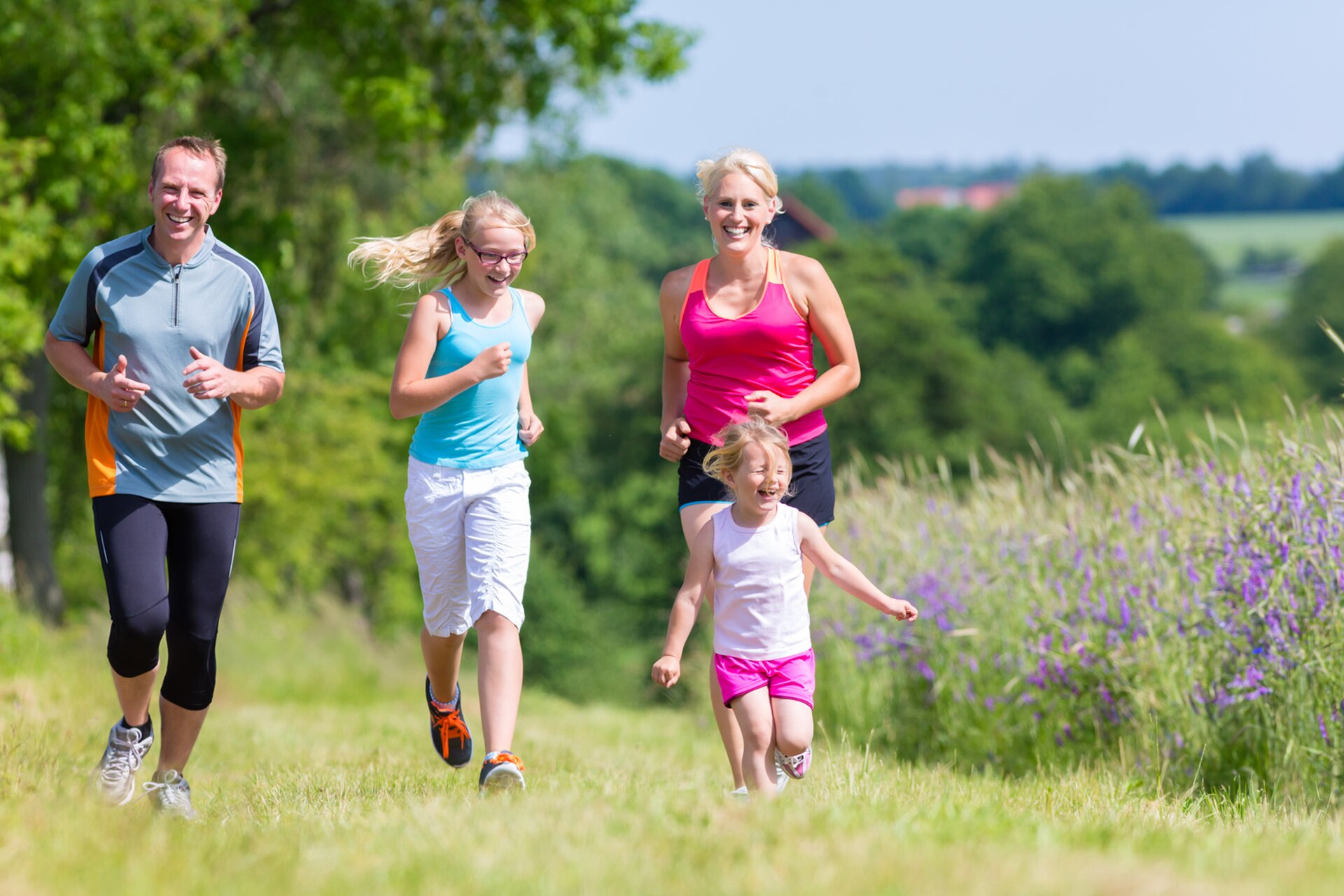 Rodzina uprawiająca biegi na świeżym powietrzu. Na fotografii widoczni biegnący rodzice, apomiędzy nimi dwie dziewczynki, wysoka strasz iniska młodsza.