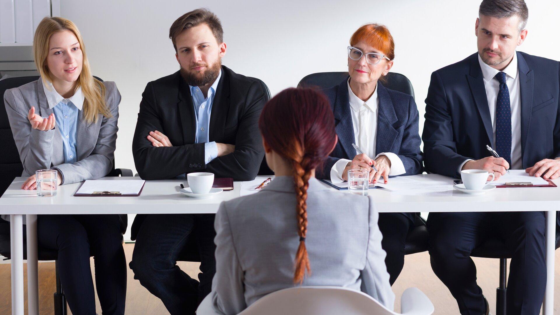 Zdjęcie przedstawia kilka postaci siedzących przy biurku. Wszyscy są ubrani elegancko. Naprzeciwko widza siedzą cztery osoby – dwie kobiety idwóch mężczyzn. Rozmawiają zkobietą siedzącą po drugiej stronie biurka. Ma kasztanowe włosy zaplecione wwarkocz iszarą marynarkę. Najprawdopodobniej zdjęcie przedstawia rozmowę kwalifikacyjną.