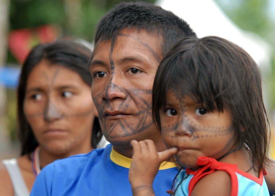 Na zdjęciu trzyosobowa rodzina, ciemne włosy, twarze pomalowane ciemna farbą wpaski ikropki.