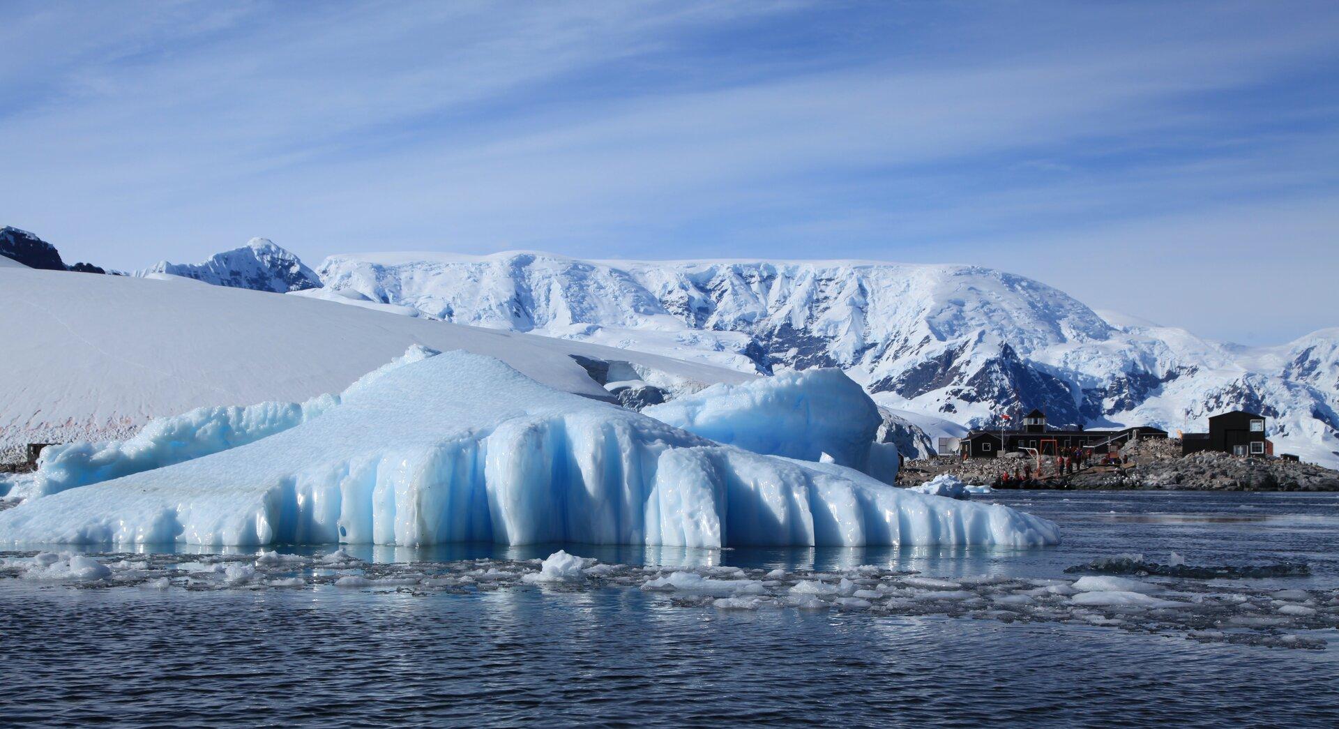 Na pierwszym planie morze. Dalej bryła lodu wystająca zwody iośnieżony brzeg. Wtle ośnieżone góry. Ustóp gór zabudowania na jedynym nieośnieżonym fragmencie gruntu.