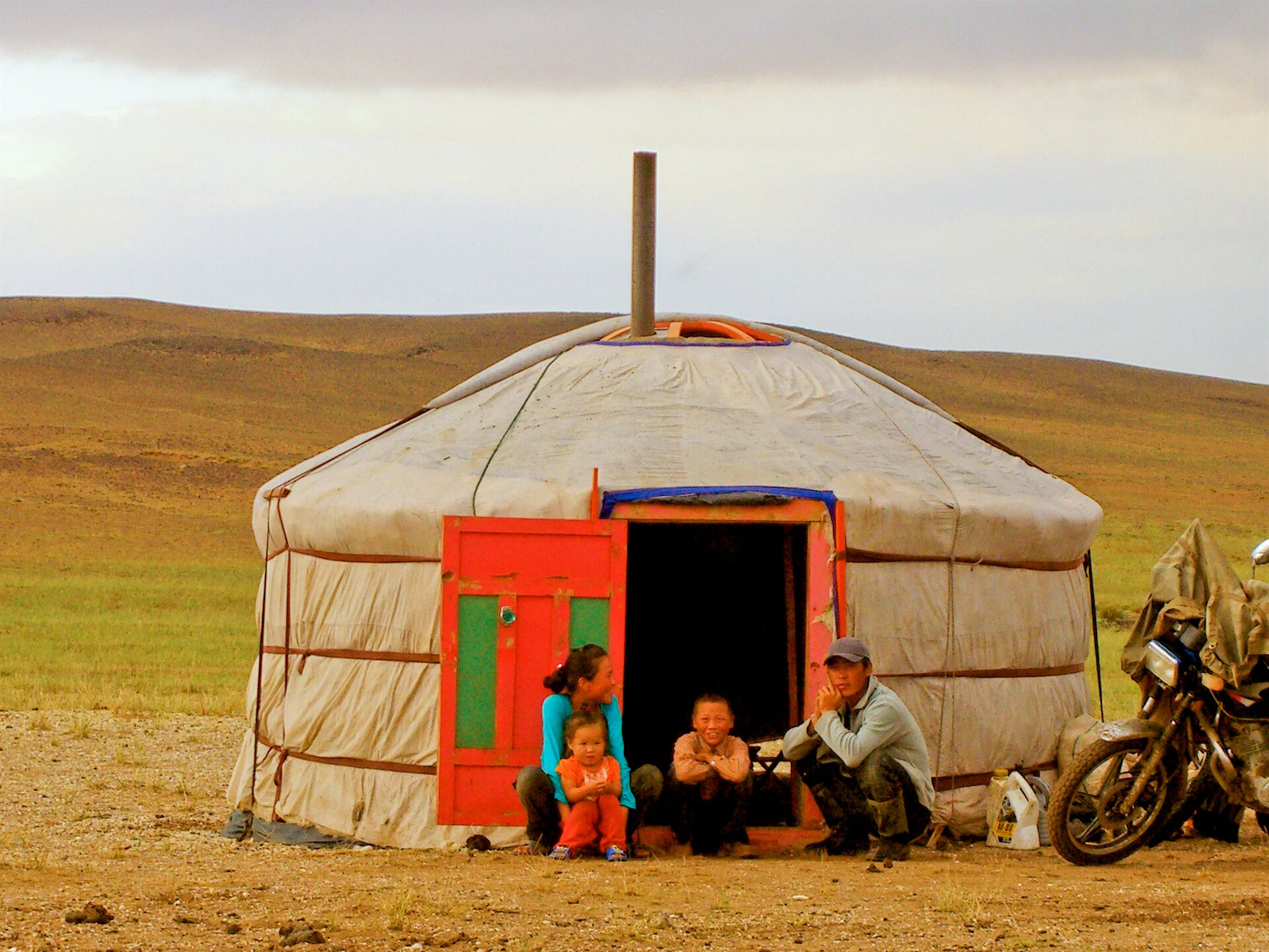 Na zdjęciu jurta na stepie wMongolii. Otwarte drzwi, przed drzwiami siedzą cztery osoby – rodzina – dwoje dorosłych idwoje dzieci. Zprawej strony zaparkowany motocykl.