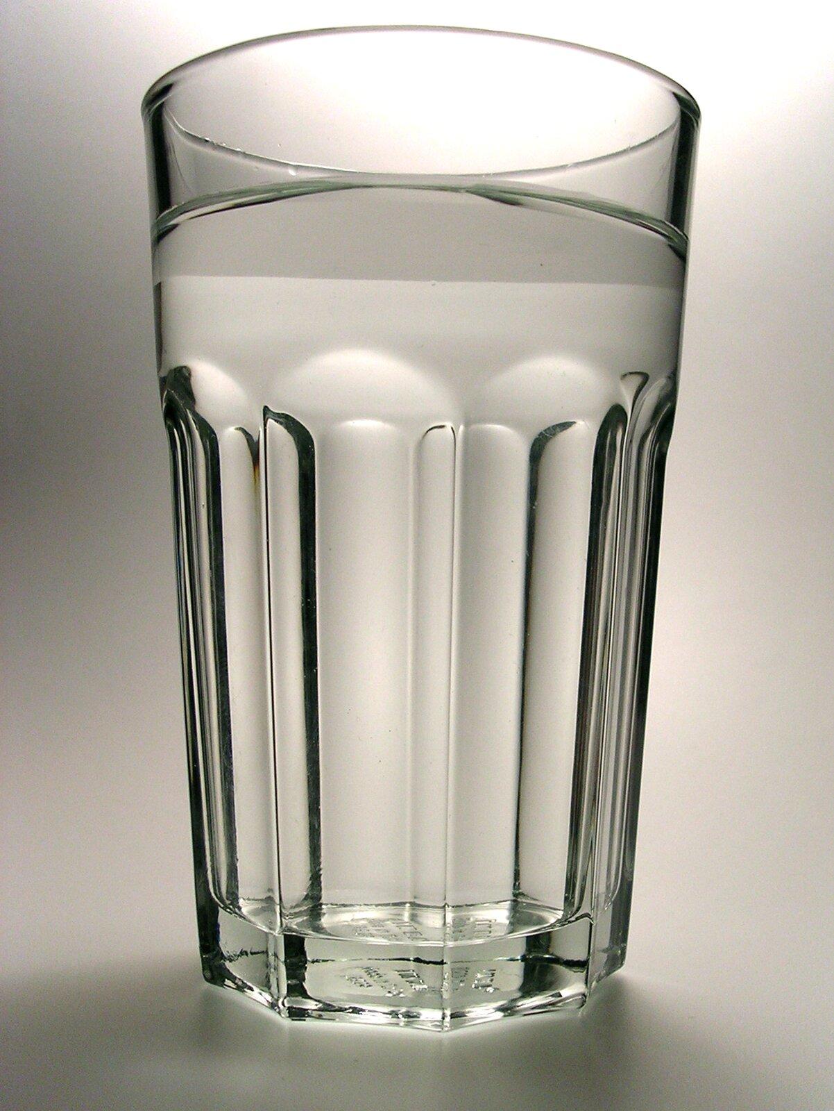 Zdjęcie przedstawia szklankę wypełnioną wodą stojącą na szarym tle.