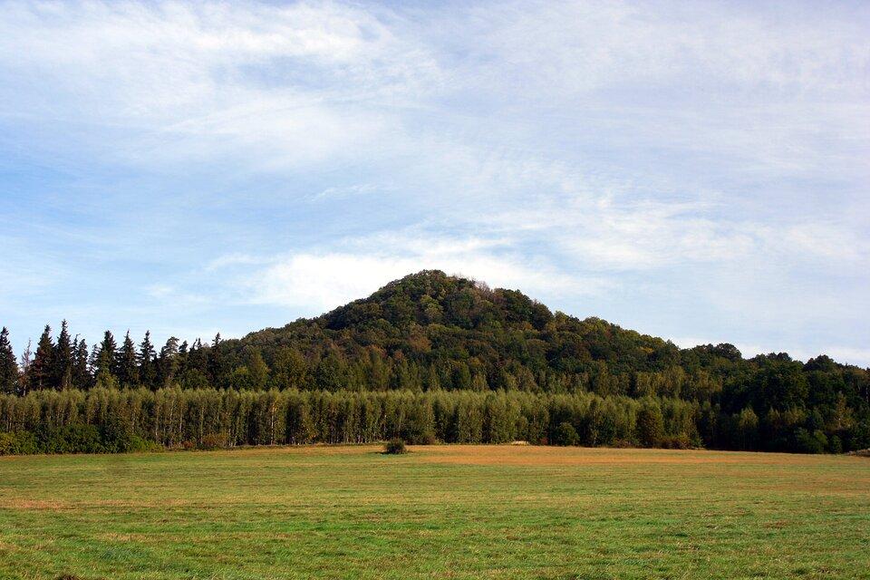 Na zdjęciu pojedyncze wzniesienie porośnięte lasem na środku równinnego terenu.