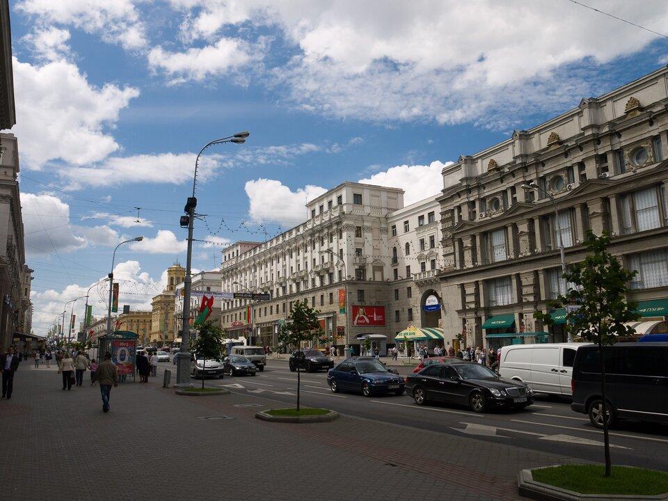 Zdjęcie przedstawia szeroką, reprezentacyjną ulicę stolicy Białorusi – Mińska. Piękne, zdobione kamienice. Na kilkupasmowej jezdni samochody, po szerokich chodnikach spacerują ludzie.