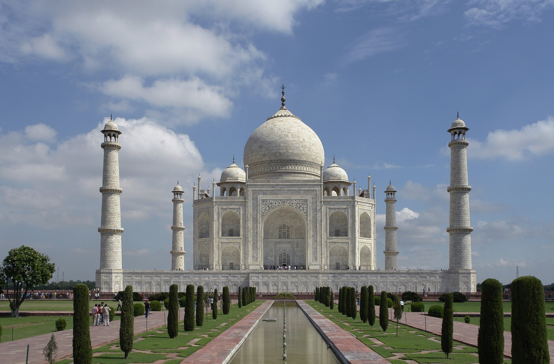 Na zdjęciu okazała, bogato zdobiona biała świątynia zwieloma kopułami iwieżami. Ogrodzona wysokim murem. Przed nią długi zbiornik wodny, wzdłuż niego strzeliste rośliny. Szerokie aleje, grupa ludzi.