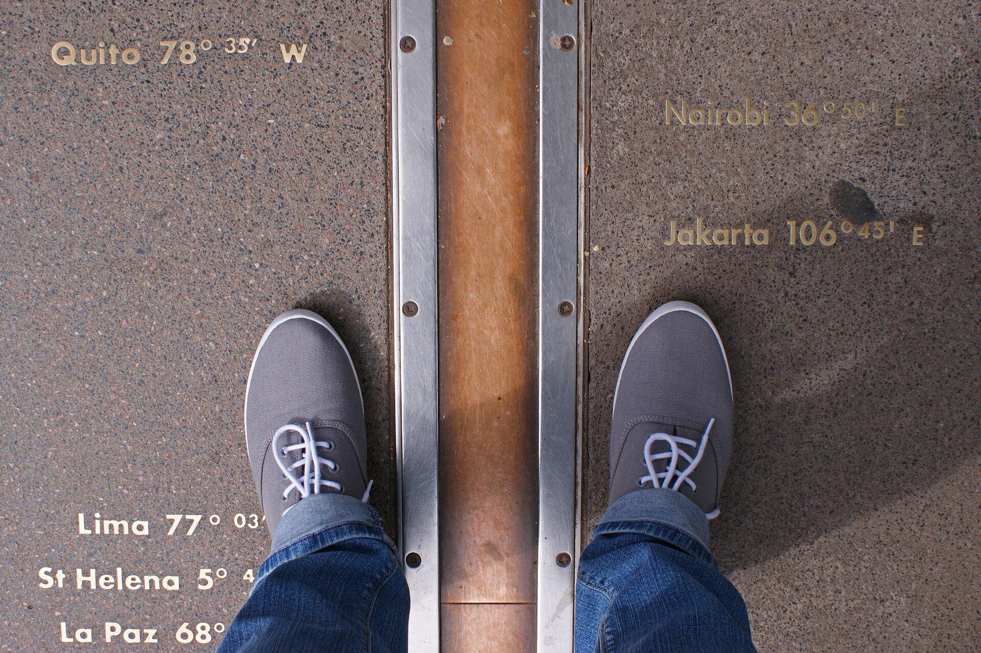 Na fotografii widać asfaltową powierzchnię. Widać stopy fotografia. Między stopami znajduje się wtopiona wasfalt metalowa wstęga oznaczająca południk zerowy.