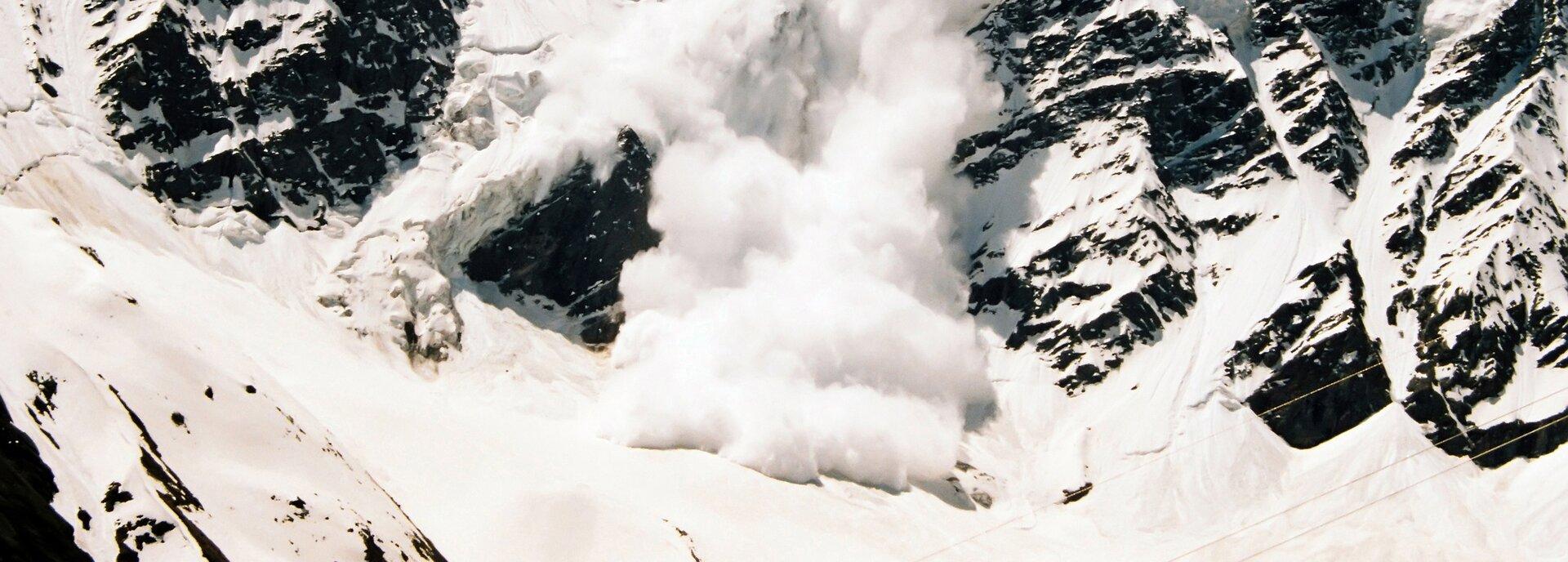 Zdjęcie przedstawia lawinę śnieżną schodzącą zwysokich gór. Wczęści centralnej zdjęcia lawina schodzi szeroko, powodując unoszenie się kłębów śniegu. Przed schodzącą lawiną powierzchnia śniegu jest gładka ipłaska. Po bokach schodzącej lawiny znajdują się ostre iciemne górskie skały, częściowo ośnieżone.