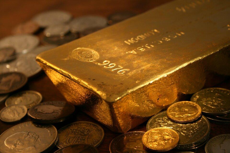 Zdjęcie przedstawia fragment sztaby złota ułożonej wotoczeniu monet. Na złocie widoczne są liczne grawerunki, choć wpełni wyraźna jest tylko liczba 9976 naniesiona wpobliżu krawędzi sztabki.
