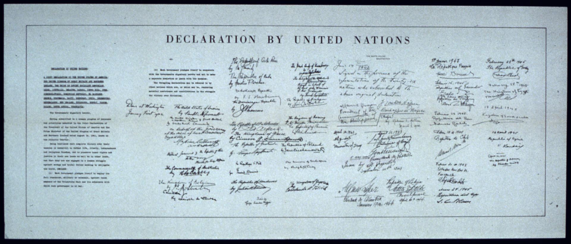 Ilustracja przedstawia duży papierowy dokument. To biało-czarne zdjęcie karty Narodów Zjednoczonych. Na górze dokumenty poziomy napis wjęzyku angielskim: declaration by United Nations. Po lewej stronie treść deklaracji wdwóch kolumnach. Na prawo od treści 26 podpisów wykonanych przez przedstawicieli państw członków założycieli. Podpisy ułożone są w7 kolumnach. Kolumny jedna obok drugiej.
