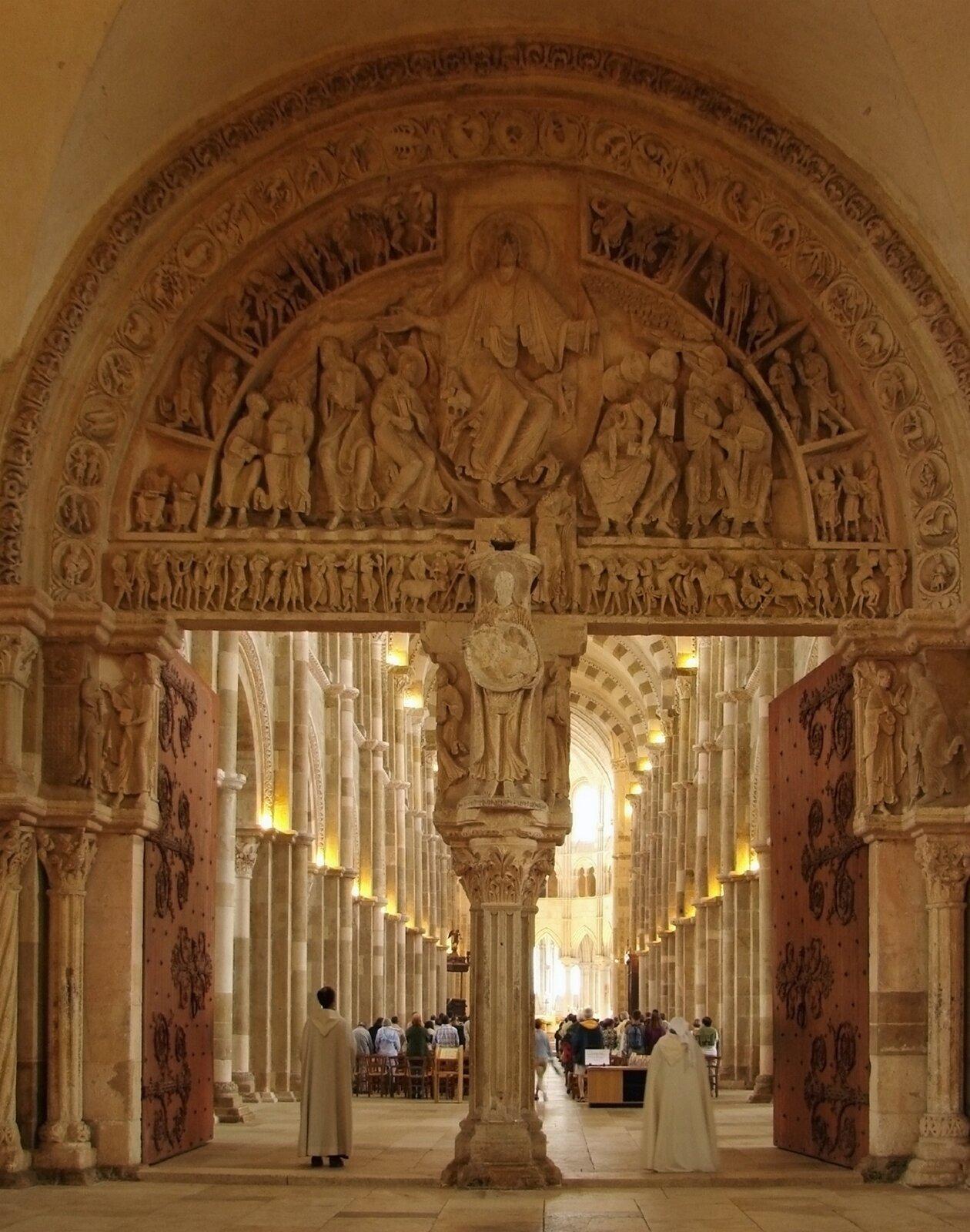 Ilustracja okształcie pionowego prostokąta przedstawia portal romański wbazylice św. Marii Magdaleny we Francji. Bazylika pochodzi zXII wieku. Na uwagę zasługuje tympanon dekorowany płaskorzeźbą oraz kolumna dzieląca wejście zrzeźbami figuralnymi. Archiwolty zdobione są motywami roślinnymi ifiguralnymi. Wościeżach znajdują się kolumny zakończone figurami. NA zdjęciu widoczne jest także oświetlone wnętrze zfragmentem sklepienia kolebkowego ifilarami dzielącymi nawę główną od bocznych.