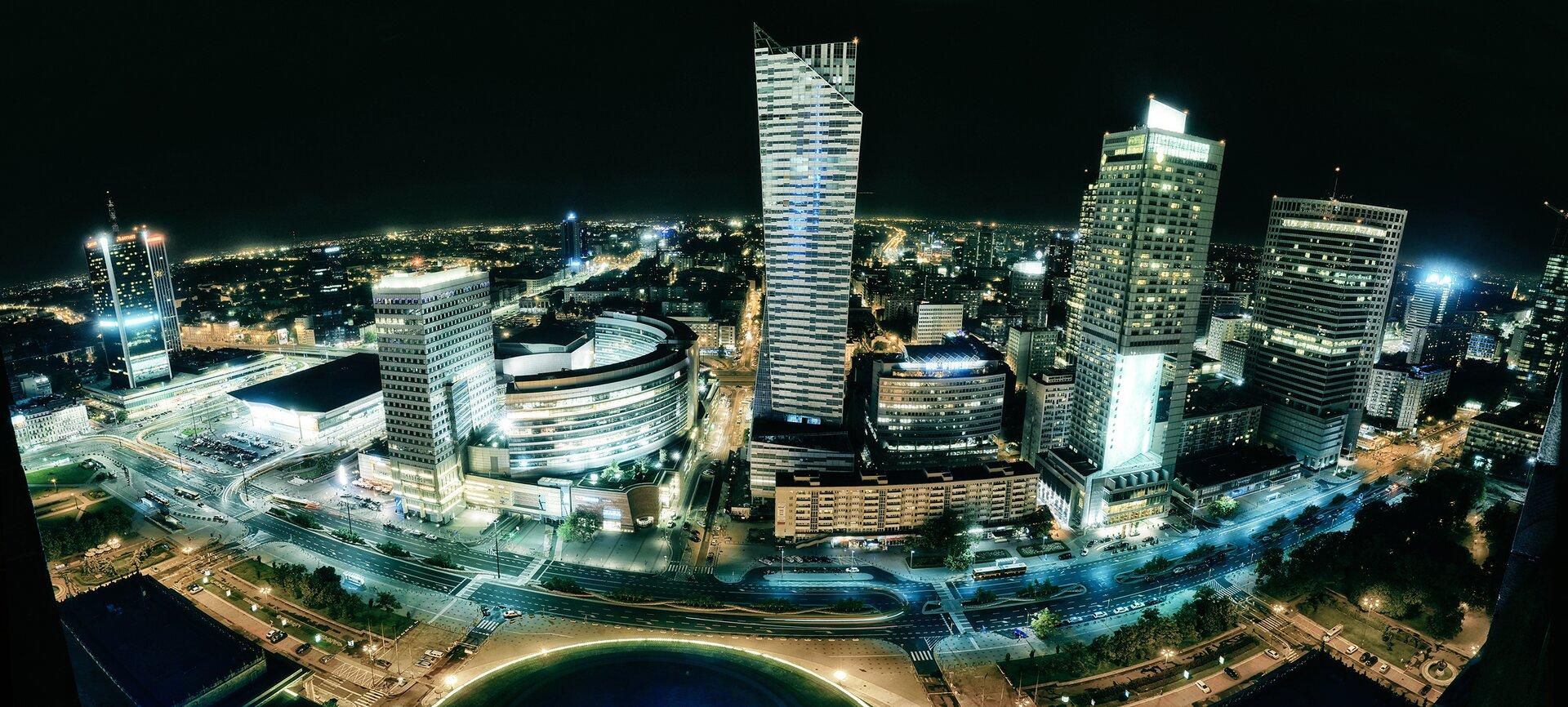 Nocna fotografia Warszawy wykonana zwysokości. Widoczne oświetlone wieżowce oraz ulice miasta.