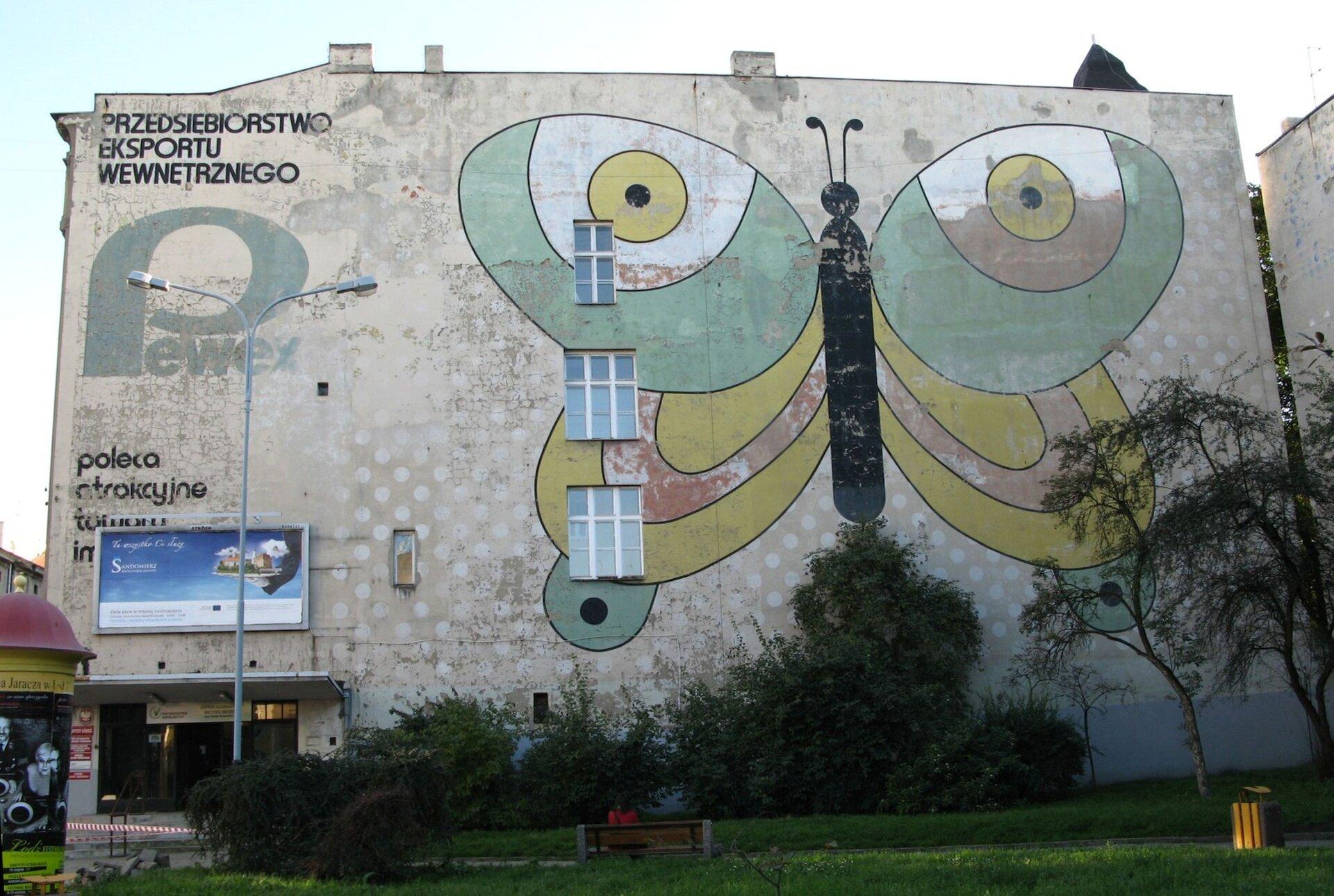 """Zdjęcie przedstawia ścianę budynku dawnego Pewexu zmuralem wkształcie motyla. Po lewej stronie budynku widnieje napis """"Przedsiębiorstwo eksportu wewnętrznego"""". Budynek ma trzy okna. Motyl namalowany jest wkolorach - zielony, żółty, czerwony oraz czarny. Przed budynkiem ukazana jest ławka oraz żółty śmietnik."""