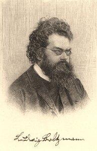 Zdjęcie przedstawia Ludwiga Boltzmanna. Zdjęcie czarno białe. Mężczyzna wwieku około czterdzieści lat. Tęga budowa ciała. Włosy ciemne długie. Gładko zaczesane do tyłu. Uszy duże. Czoło gładkie wysokie. Widoczne zakola. Nos duży. Gęsta kręcona broda krótka łączy się zbokobrodami. Dłuższa poniżej ust. Wąsy czarne zakrywają górną wargę. Okulary zmałymi okrągłymi oprawkami. Twarz skierowana nieco wlewo. Mężczyzna urany wbiałą koszulę, ciemną kamizelkę imarynarkę.