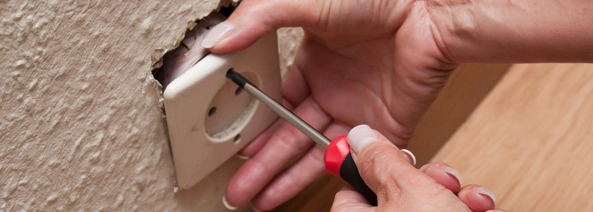 Kolorowe zdjęcie przedstawia wyjęte ze ściany gniazdko elektryczne podtrzymywane przez jedną dłoń. Osoba podtrzymująca gniazdko ma wdrugiej dłoni śrubokręt włożony wotwór, którym można gniazdko przymocować do ściany.