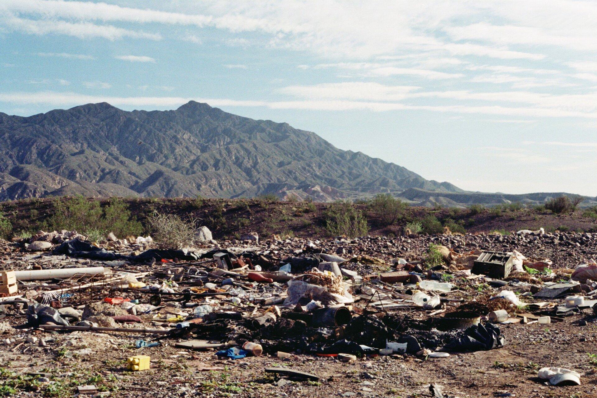Fotografia przedstawia krajobraz zgórami wtle. Na pierwszymplanie mnóstwo leżących na ziemi śmieci. Są to odpady domowe, mebelki, zabawki, plastikowe części, nadpalone przedmioty. Widok robi przygnębiające wrażenie. Dlaczego wokół nas jest tyle śmieci?