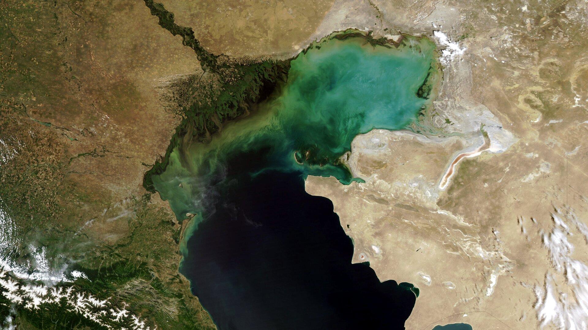Na zdjęciu lotniczym fragment Morza Kaspijskiego. Ciemnoniebieska toń woda, przy brzegu turkusowa. Lewy brzeg porośnięty roślinnością, prawy brzeg piaszczysty.