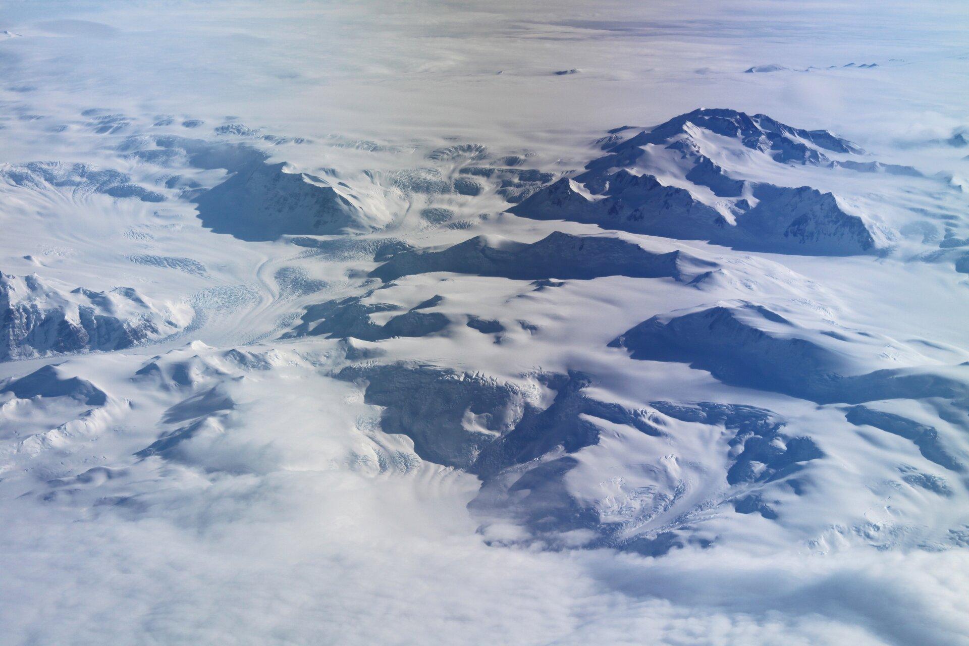 Fotografia prezentuje górzysty krajobraz lodowy na Antarktydzie.