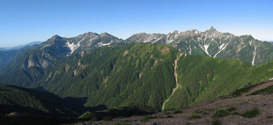 Na zdjęciu wysokie pasmo górskie porośnięte roślinnością, szczyty skaliste.