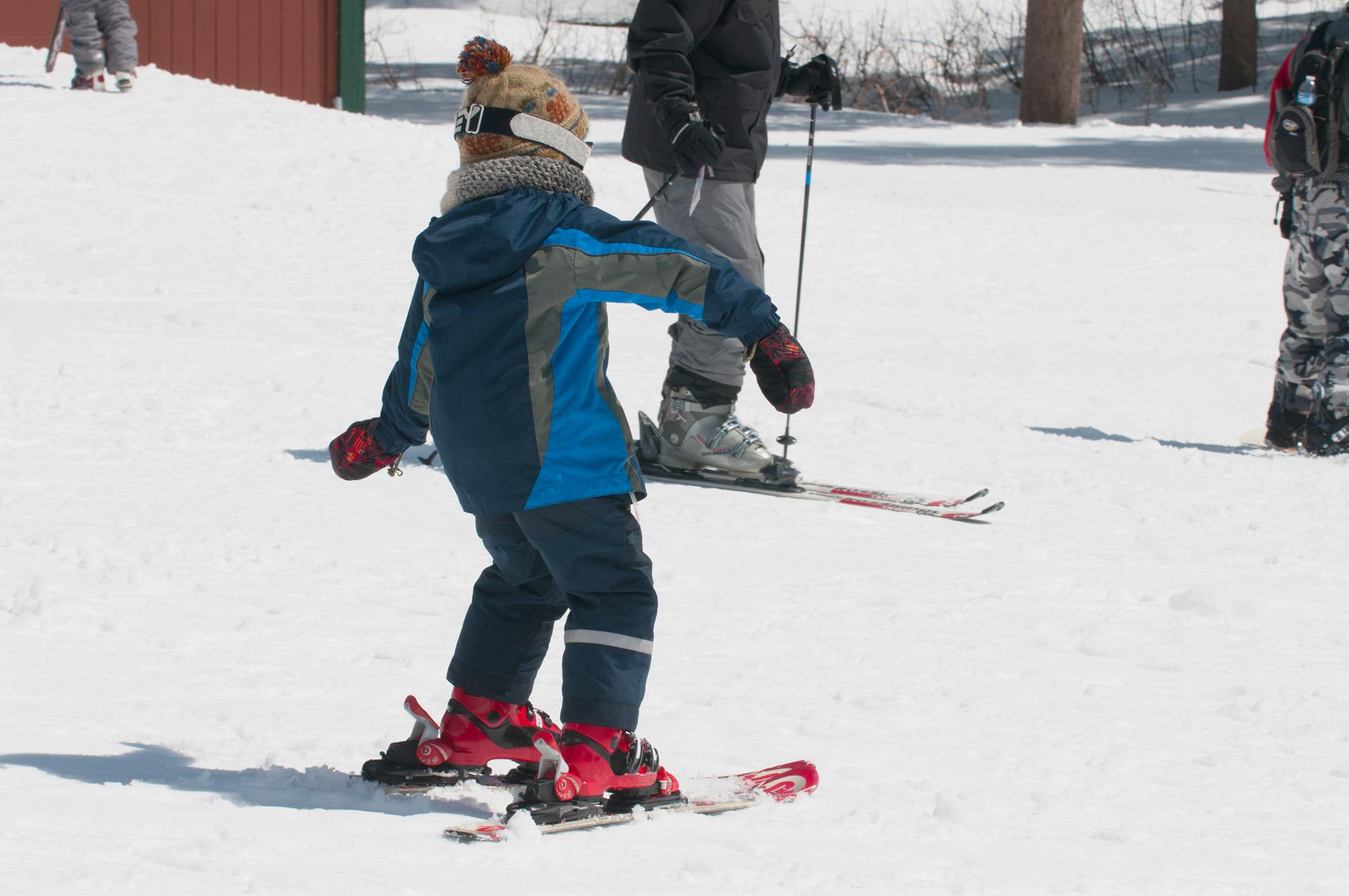 Fotografia przedstawia na pierwszym planie dziecko próbujące zjeżdżać na nartach po łagodnym, ośnieżonym stoku.