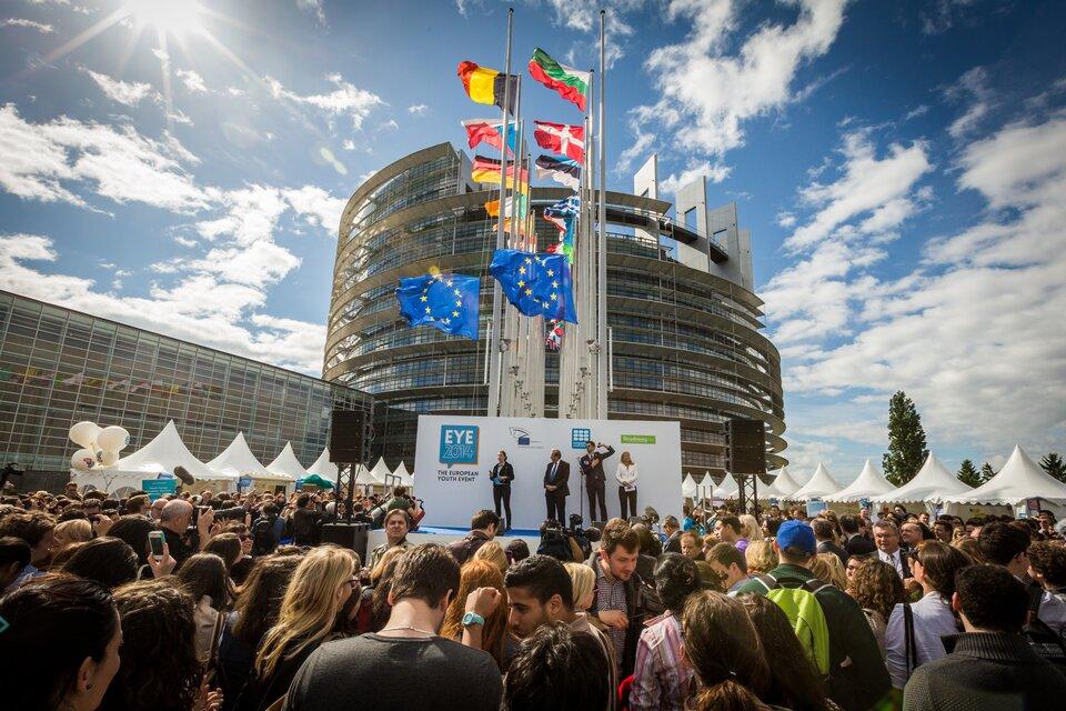 Na zdjęciu wtle widoczny gmach Parlamentu Europejskiego wStrasbourgu. Przed nim wysokie maszty iflagi państw Unii Europejskiej isamej Unii. Na pierwszym planie scena. Na scenie czworo ludzi. Wokół sceny tłumy ludzi.