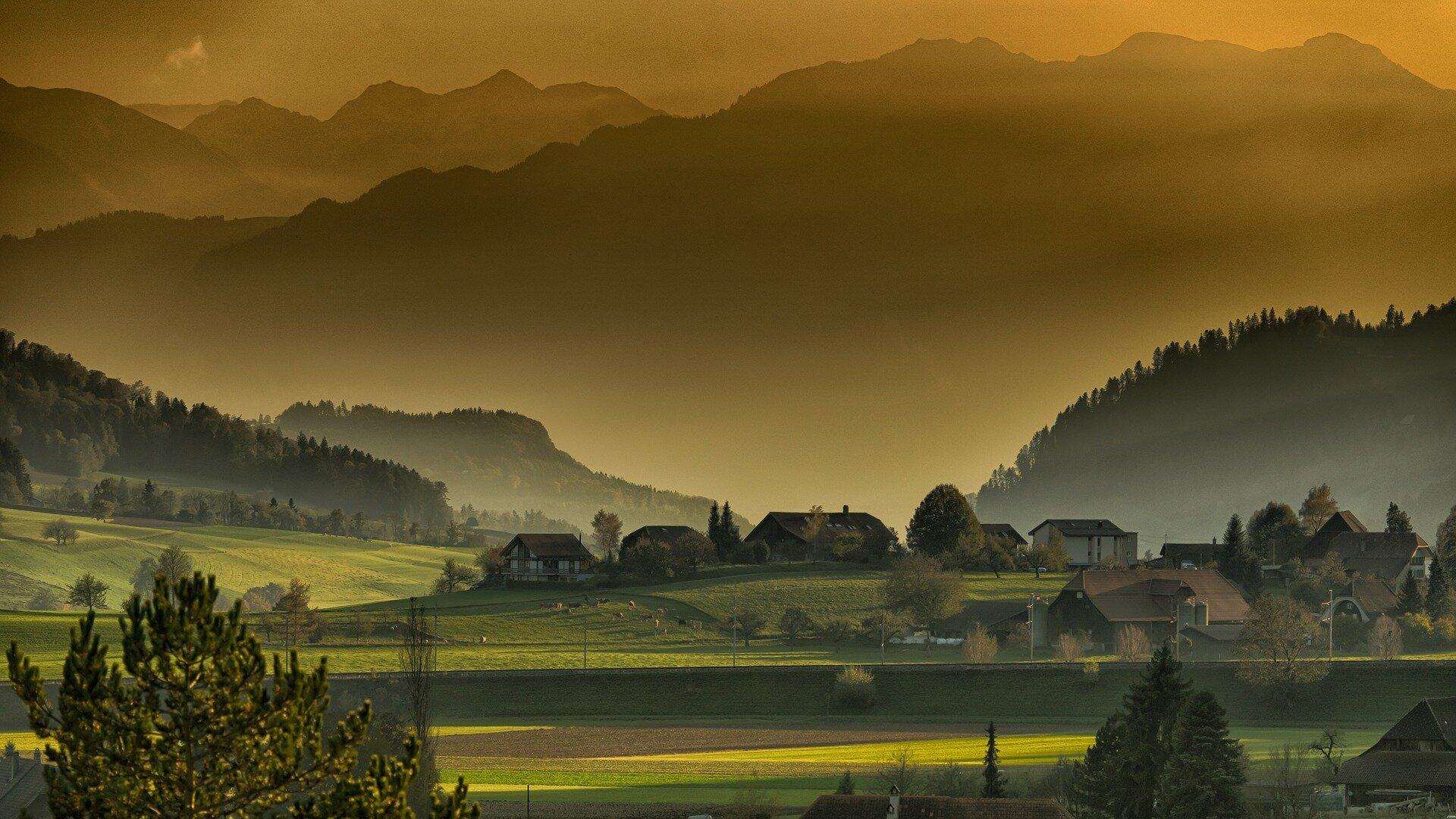 Zabudowania wiejskie stojące wśród zielonych pól. Pośród domów stoją drzewa, na łące pasą się zwierzęta. Wbliskim tle, są pola ilasy na zboczach wzgórz, adaleko wtle są szczyty wysokich gór iskał.