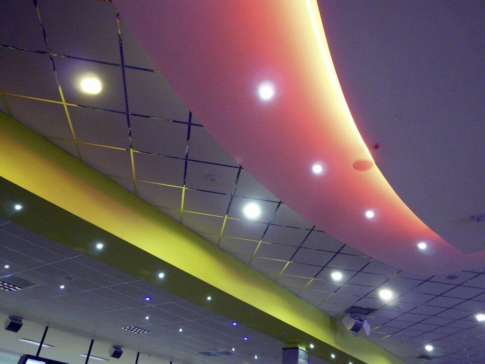 Zdjęcie przedstawia sufit weleganckiej sali biurowej lub prezentacyjnej. Widoczne liczne lampki zapewniające tak zwane oświetlenie punktowe umieszczone zarówno na suficie, jak ipodwieszanych pod nim elementach dekoracyjnych. Łącznie około trzydziestu punktów świetlnych białych iniebieskawych.