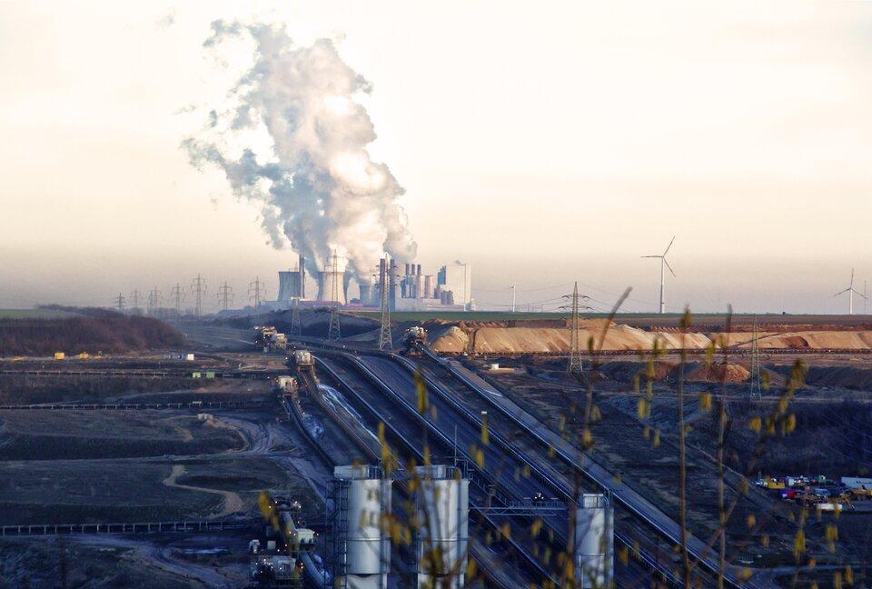 Fotografia przedstawia krajobraz przemysłowy. Na pierwszym planie kominy zakładów oraz szerokie drogi dojazdowe zwyrobiskami po obydwu stronach. Woddali liczne dymiące kominy.