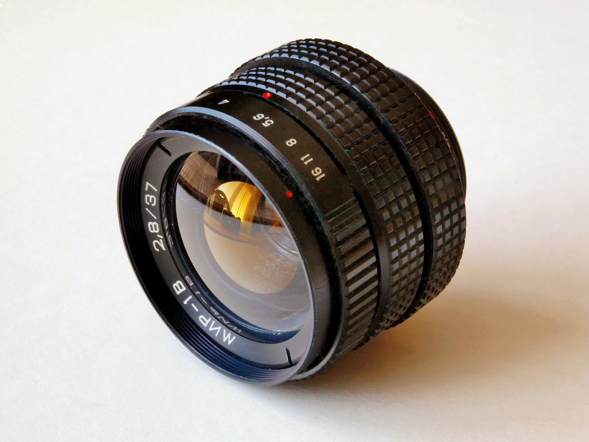 Zdjęcie przedstawia fotograficzny obiektyw manualny stałoogniskowy rosyjskiej produkcji, na co wskazują oznaczenia modelu MIR-1B, napisane cyrylicą. Widoczna przednia soczewka, wktórej odbija się zawartość pokoju, m.in. okno zzasłonami ikrzesło, oznaczenia parametrów jasność dwa przecinek osiem, długość ogniskowej trzydzieści siedem milimetrów. Widoczne są też dwa metalowe karbowane pierścienie kontrolne: ogniskowej iwartości przysłony.