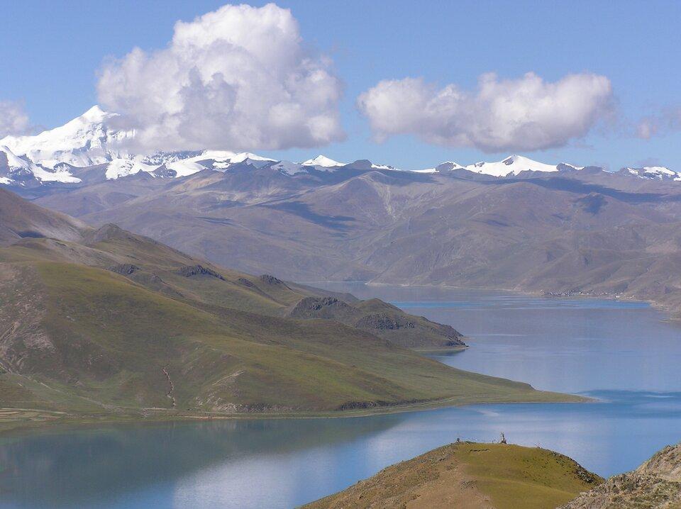 Na zdjęciu zbiornik wodny, dookoła łagodne zbocza, wtle pasmo górskie pozbawione roślinności, szczyty ośnieżone.