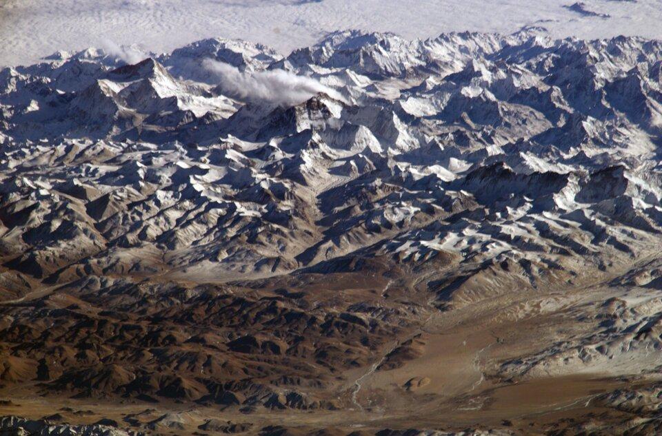 Na zdjęciu obszar górzysty, pofałdowany. Widok zlotu ptaka. Na pierwszym planie niższe góry wkolorze brązowym. Na dalszym planie wysokie góry pokryte śniegiem. Jeszcze dalej góry zakryte białą warstwą chmur.