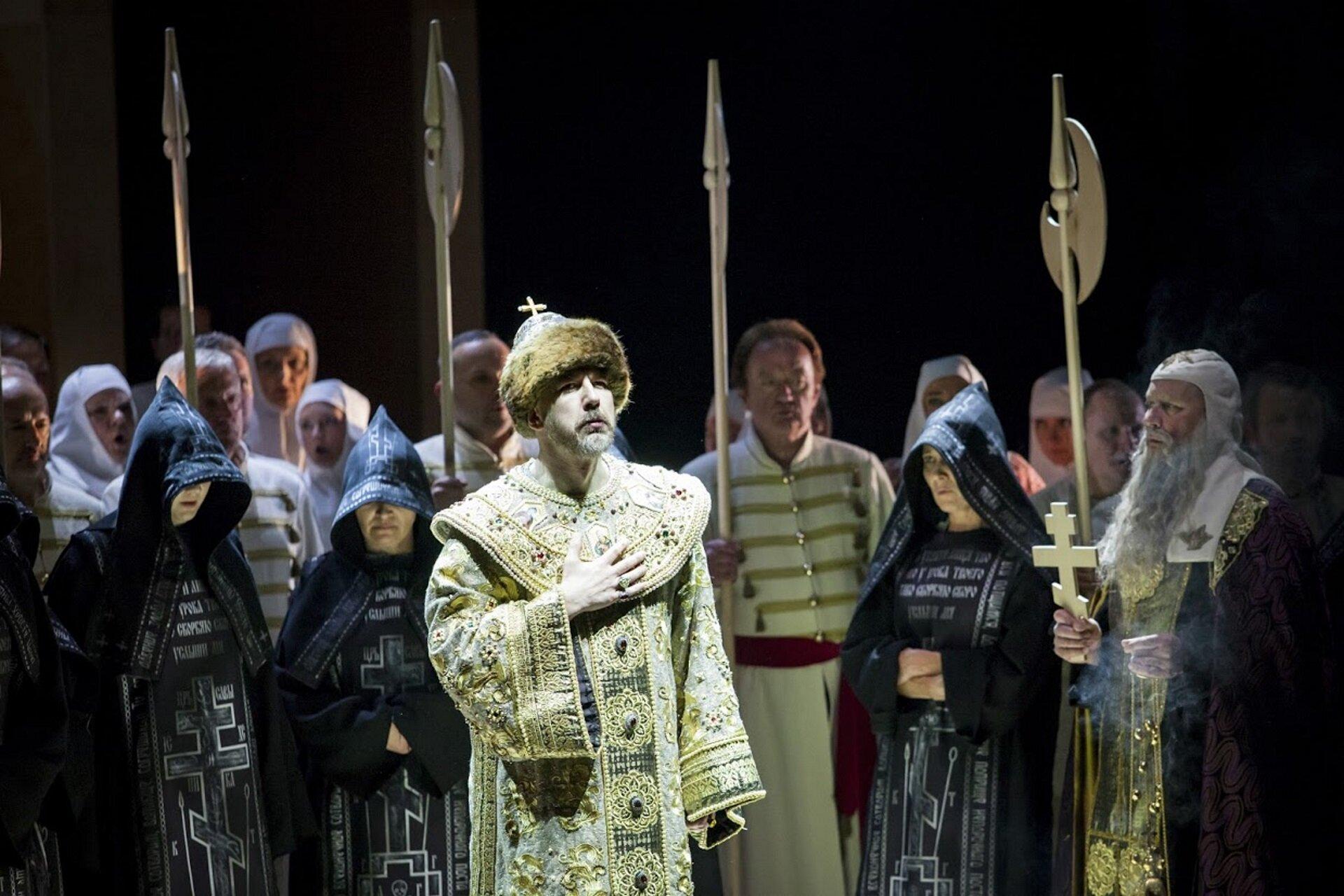 """Ilustracja przedstawia scenę zopery Modesta Musorgskiego """"Borys Godunow"""". Na zdjęciu widzimy mężczyznę wjasnym, zdobionym płaszczu, na głowie ma czapkę zfutra oraz zamocowany krzyż. Za nim stoją postaci wczarnych szatach zkapturami na głowie. Wdalszej części zdjęcia znajdują się mężczyźni zdługimi sztyletami oraz zakonnice wbiałych strojach. Po prawej stronie jest starzec zdługą, siwą brodą, który wręce trzyma biały, drewniany krzyż."""