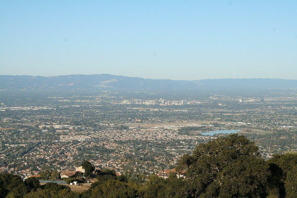 Na zdjęciu rozległa dolina, gęsta zabudowa, wtle góry.